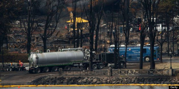 LAC-MEGANTIC QC - JULY 9: A mobile labratory operated between oil spill booms and the derailed train...