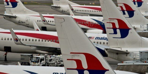 Airport groundstaff walk past Malaysia Airlines planes parked on the tarmac at the Kuala Lumpur International...
