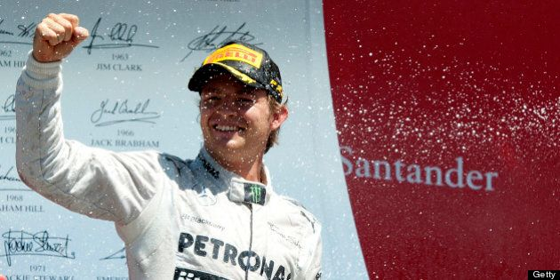 Mercedes' German driver Nico Rosberg celebrates his victory on the podium at the Silverstone circuit...
