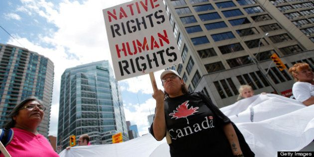 TORONTO, ON - JUNE 24: A woman holds a sign as several hundred indigenous people march through the streets of Toronto to bring attention to the plight of indigenous peoples in Canada two days prior to the opening of the G20 Summit on June 24, 2010 in Toronto, Canada. Leaders from the world's 20 largest industrial and developing nations are arriving in Toronto for the G20 Summit scheduled to be held June 26 and 27. (Photo by Jemal Countess/Getty Images)