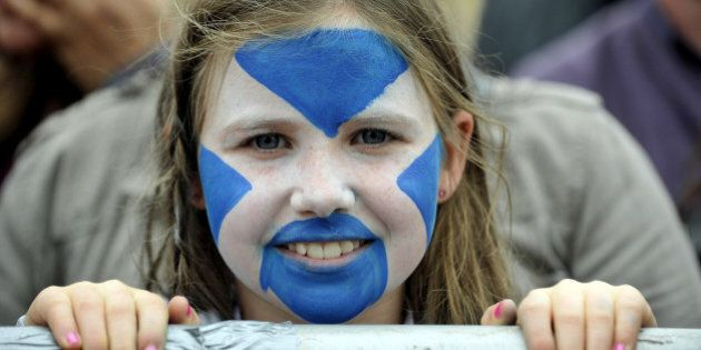 A child with her face painted with the Scottish flag looks on as pro-independence supporters gather for...