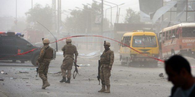 Afghan security personnel walk at the site of a suicide car bomb attack on the convoy of Afghan presidential...