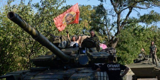 Pro-Russian fighters sit ontop of a tank in Starobesheve, southeast of Donetsk, on August 31, 2014. Pro-Russian...
