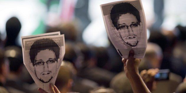 Demonstrators holding papers to be cut to make portraits of Edward Snowden protest during the opening...