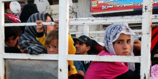 Syrian refugees flee from the Lebanese eastern town of Arsal on their way to cross back into Syria, as...