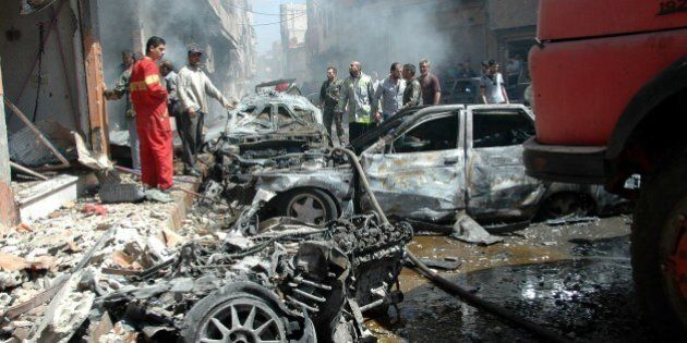Emergency personnel and civilians inspect the site following a car bomb explosion in the Abbasiyah neighbourhood...