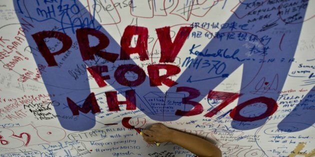 A Malaysia Airlines employee writes a message expressing prayers and well-wishes for passengers onboard...