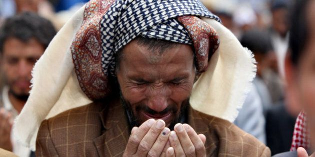 A Yemeni anti-government protester performs the noon prayers during a demonstration against the regime...