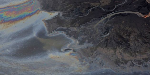 Oils mixes with water at a tailings pond at a Suncor Energy Inc. oil sands mining operation near Fort...