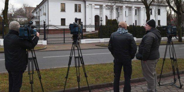 News cameramen wait outside the presidential residence in Minsk on December 24, 2014, as fresh round...