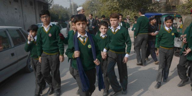 PESHAWAR, PAKISTAN - DECEMBER 16: Pakistani students walk near the site of an attack by Taliban gunmen...