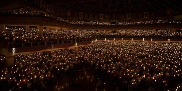 In this picture taken on December 24, 2014 Christians hold candles during the mass service in Surabaya,...