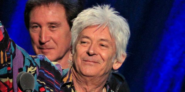 Ian McLagan, right, holds up his trophy after he and Ron Wood, left, and Kenney Jones, background, were...