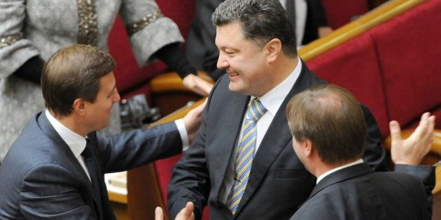 Ukraine's newly elected Foreign Minister Petro Poroshenko (C) is congratulated by deputies in parliament...