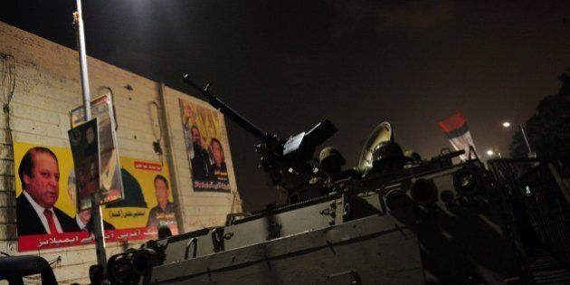 Pakistani troops take position with an armored vehicle at he Karachi airport terminal after the militants'...