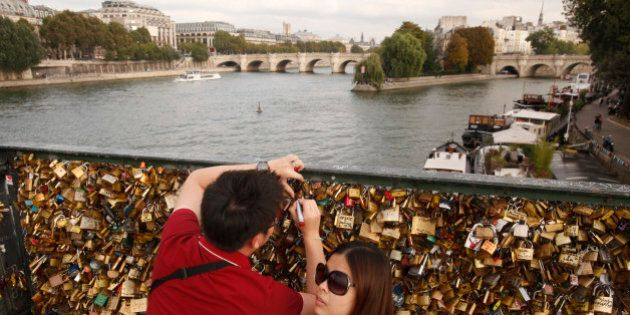 PARIS, FRANCE- JANUARY 30: A couple write upon a lock on the Pont-Des-Arts Bridge on January 30, 2013...