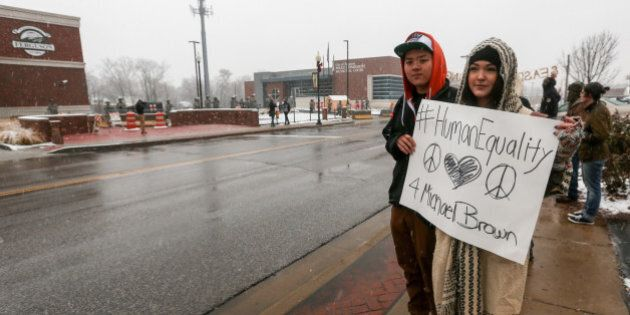 FERGUSON, UNITED STATES - NOVEMBER 26: People hold banners reading 'Human Equality' as National Guard...