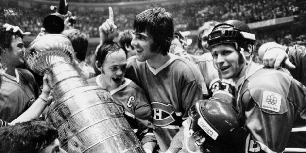 Yvan Cournoyer, captain of the Montreal Canadiens, holds the Stanley Cup as he is surrounded by teammates...