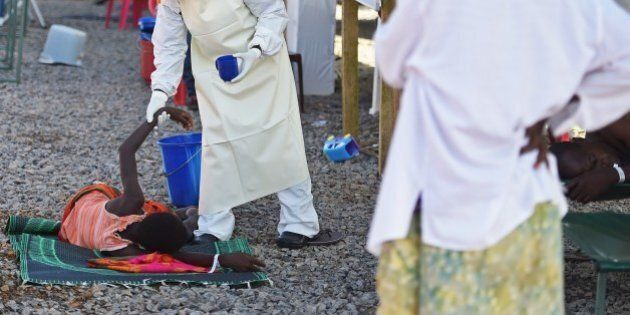 A health worker wearing protective equipment assists an Ebola patient at the Kenama treatment centre...