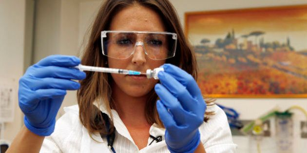 Dr Felicity Hartnell, who is a clinical research fellow at Oxford University, holds a vial of an experimental...