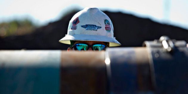 A Michels Corp. contractor watches as two sections of pipe are prepped for welding during construction...