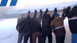 Des passagers poussent leur avion gelé pour le faire décoller