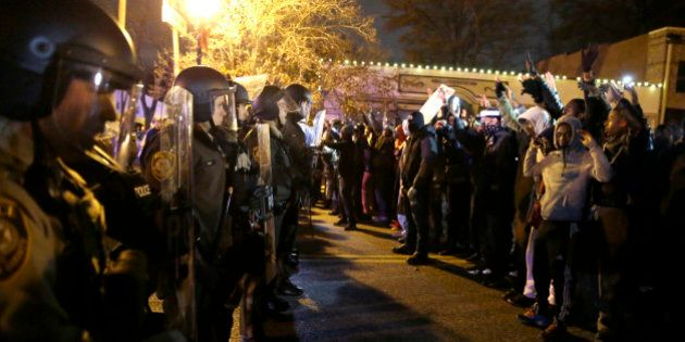 Police officers stand guard as protesters react to the announcement of the grand jury decision not to...