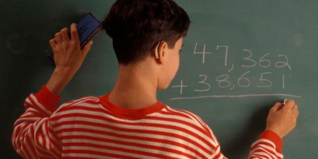 Hearing Impaired boy writing a math equation on a chalkboard (Photo by: Digital Light Source/UIG via...