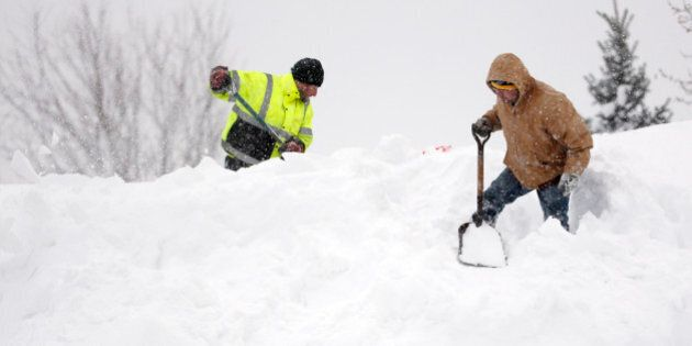 Mark Settlemyer, left, gets help clearing snow from the roof of his mother's house from Ken Wesley on Wednesday, Nov. 19, 2014, in Lancaster, N.Y. Lake-effect snow pummeled areas around Buffalo for a second straight day, leaving residents stuck in their homes as officials tried to clear massive snow mounds with another storm looming. (AP Photo/Mike Groll)
