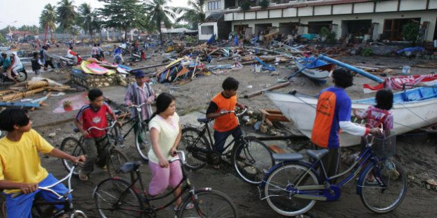 Indonesians push their bicycle through a tsunami-devastated area in Pangandaran, West Java, Indonesia,...