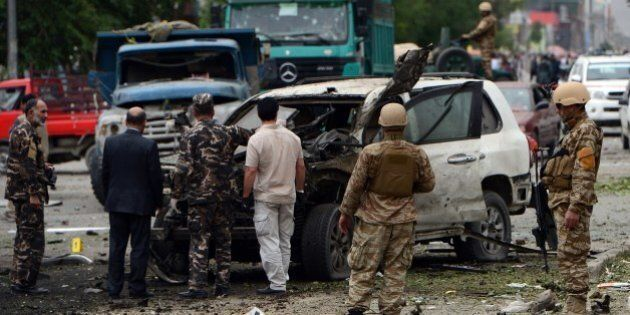 Afghan investigators inspect a damaged car at the site of a suicide car bomb attack on the convoy of...