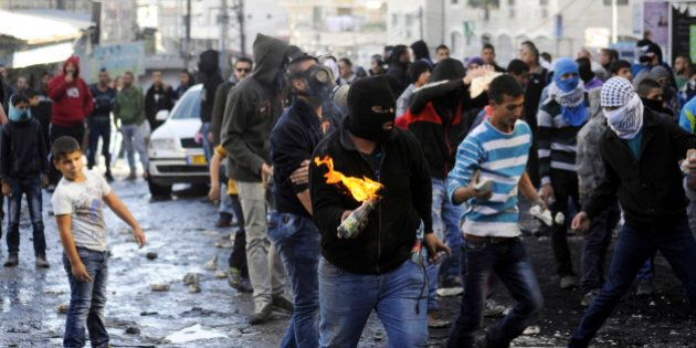 A Palestinian holds a molotov cocktail during clashes with Israeli border police, as Israeli police limited...