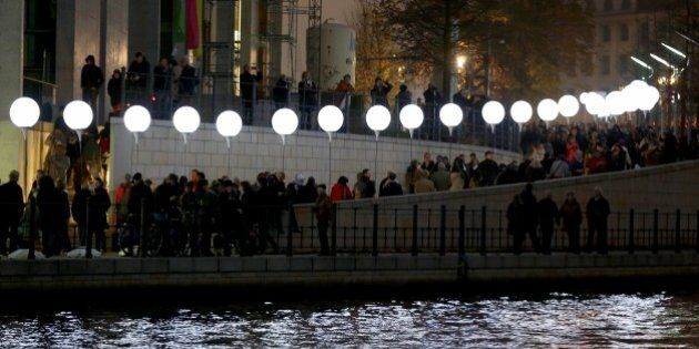 BERLIN, GERMANY - NOVEMBER 09: People gather along the 15 kilometers line enlightened balloons filled...