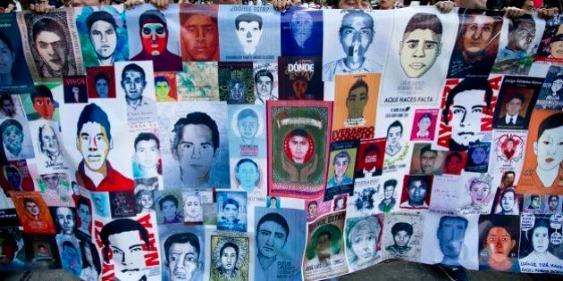 Demonstrators march holding images of missing students in protest for the disappearance of 43 students...