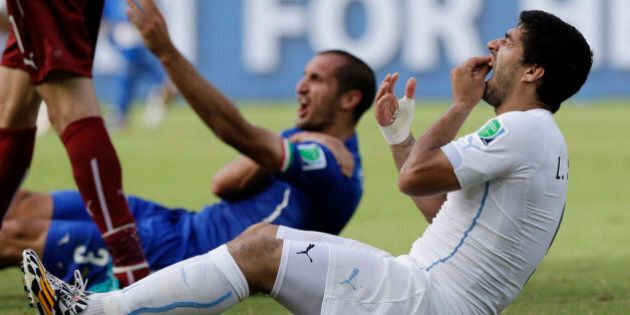 Uruguay's Luis Suarez holds his teeth after running into Italy's Giorgio Chiellini's shoulder during...