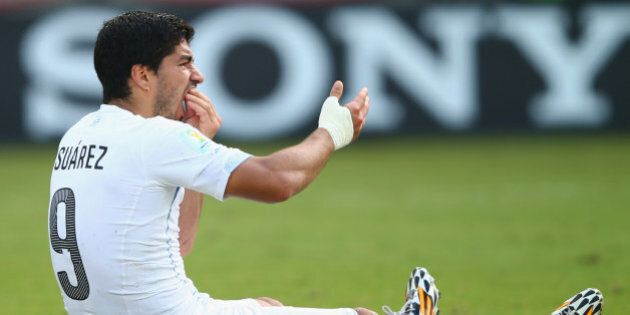 NATAL, BRAZIL - JUNE 24:  Luis Suarez of Uruguay reacts after a clash during the 2014 FIFA World Cup Brazil Group D match between Italy and Uruguay at Estadio das Dunas on June 24, 2014 in Natal, Brazil.  (Photo by Clive Rose/Getty Images)
