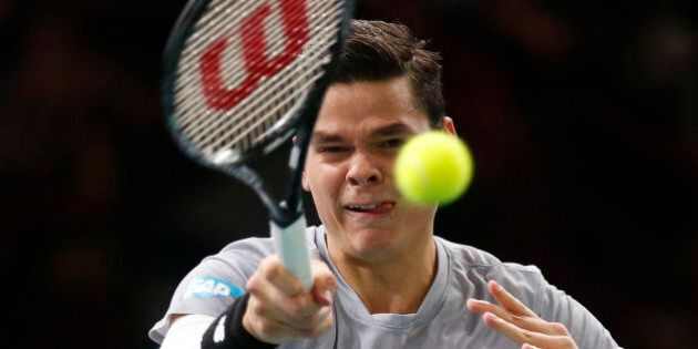 Milos Raonic of Canada returns the ball to Roger Federer of Switzerland during their quarterfinal match...