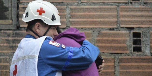A member of the Colombian Red Cross conforts a relative outside of a coal mine in the municipality of...
