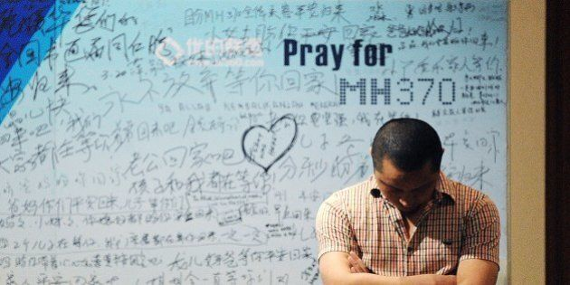 A man stands in front of a billboard in support of missing Malaysia Airlines flight MH370 as Chinese...