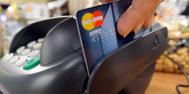 FILE - In this Nov. 2, 2009 file photo, a customer swipes a MasterCard debit card through a machine while...