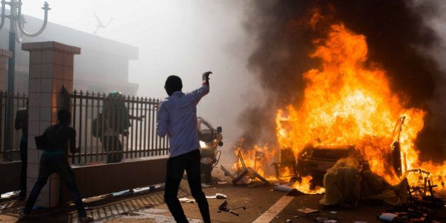 A car burns outside the parliament building in Burkina Faso as people protest against their longtime...