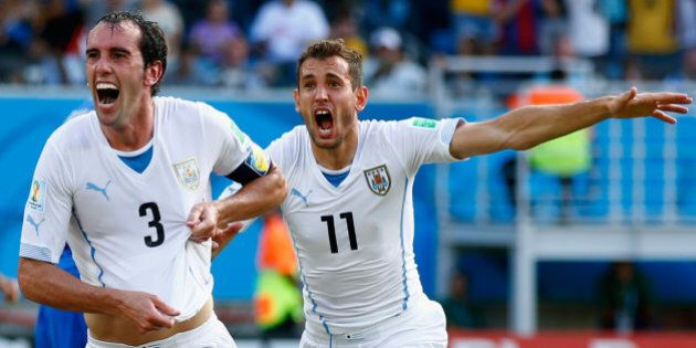 NATAL, BRAZIL - JUNE 24: Diego Godin of Uruguay (L) celebrates scoring his team's first goal during the...
