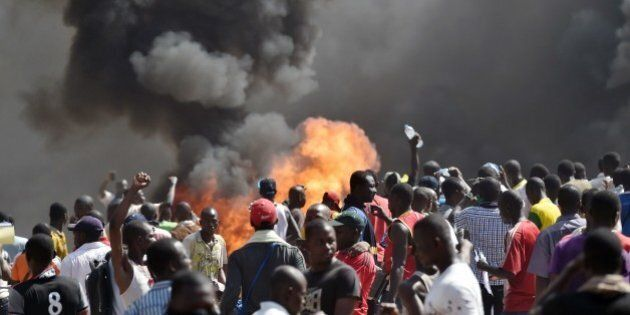 People stand in front of smoke rising from the Burkina Faso's Parliament, where demonstrators set cars...