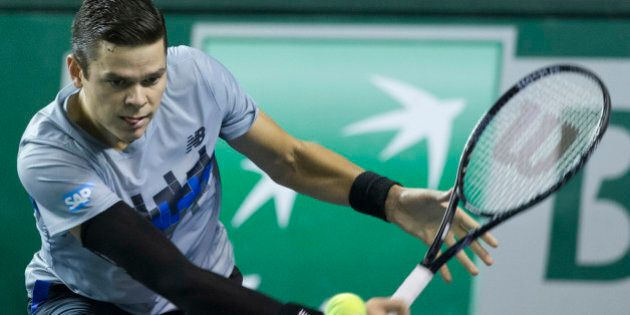Milos Raonic of Canada returns the ball to Roberto Bautista of Spain during their third round match at the ATP World Tour Masters tennis tournament at Bercy stadium in Paris, France, Thursday, Oct. 30, 2014. (AP Photo/Jacques Brinon)