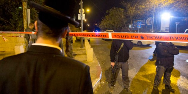 An ultra-Orthodox Jewish man looks as Israeli police officers stand guard at the scene of a shooting...