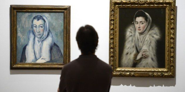 A man looks at the painting 'Lady in a Fur Wrap' (1577-78) (R) by Spanish's painter El Greco and 'Lady...