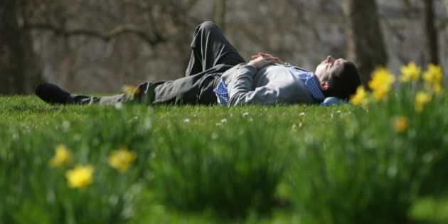 A man lies in the sun in St James's Park, London, as Londoners enjoy the warm