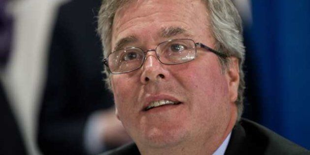 Former Florida governor Jeb Bush speaks with an admirer as he signs the book 'Immigation Wars' he co-authored...