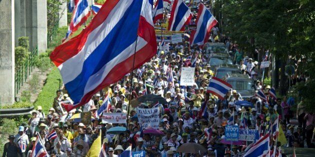 Thai anti-government protesters wave national flags during a rally in Bangkok on May 12, 2014. Thailand's authorities warned on May 11 that opposition efforts to hand power to an unelected regime risked unleashing new violence, as rival protesters prepared for a showdown over the fate of the crippled government. AFP PHOTO / PORNCHAI KITTIWONGSAKUL        (Photo credit should read PORNCHAI KITTIWONGSAKUL/AFP/Getty Images)