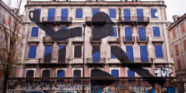 A giant man is sticking out his head and arms of the windows of an old abandoned building. The art piece...